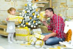 Junge Erforschungsgeschenkboxen der Vater- und Kleinkindtochter nahe verziertem Weihnachtsbaum zu Hause lizenzfreie stockbilder