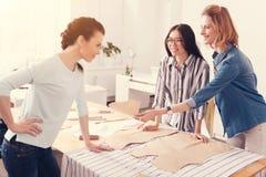 Junge erfreute Damenschneiderinnen, die im Studio arbeiten lizenzfreie stockbilder
