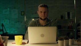 Junge ernste arbeitende späte Stunden in seinem Büro Büro ist nur sein Tabellenlicht eingeschaltet ist dunkel verschiedene Pläne  stock footage
