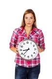 Junge ernste Frau, die Uhr hält lizenzfreie stockfotos