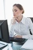 Junge ernste Geschäftsfrau, die an ihrem Schreibtisch sitzt Lizenzfreies Stockfoto