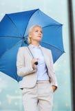 Junge ernste Geschäftsfrau mit Regenschirm draußen Stockfoto