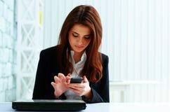 Junge ernste Geschäftsfrau, die auf ihrem Smartphone schreibt Lizenzfreie Stockfotos
