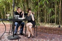 Junge ernste romantische Paare, die auf Patio speisen stockfotografie