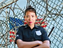 Junge ernste und attraktive asiatische amerikanische Schutzfrauenstellung an tragender Polizei Staatsgefängnisgefängnis barbwire  stockfotos