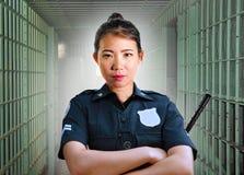 Junge ernste und attraktive asiatische koreanische Schutzfrauenstellung auf Zelle an tragender Polizeiuniform des Staatsgefängnis stockfotografie