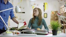 Junge erschöpfte Studentinlesebücher und Handelnhausarbeit, während andere ihre anderen Bücher holen stock video