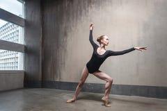 Junge erwachsene Ballerina, die ihren klassischen Tanz in einer Turnhalle probt stockbilder