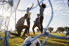 Junge Erwachsene, die einem geschossenen Tor am Fußballspiel zujubeln lizenzfreies stockfoto