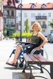 Junge erwachsene Frau auf Rollstuhl auf der Straße Lizenzfreie Stockbilder