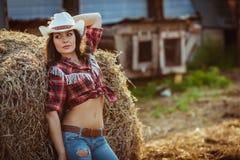 Junge erwachsene Frau, die auf Ackerland aufwirft Stockfotografie