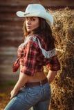 Junge erwachsene Frau, die auf Ackerland aufwirft Stockbilder