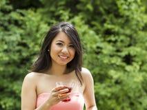 Junge erwachsene Frau, die draußen ein Getränk hält stockbild