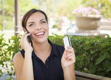 Junge erwachsene Frau, die draußen Handy und Kreditkarte hält Lizenzfreie Stockbilder