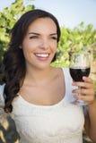 Junge erwachsene Frau, die ein Glas Wein im Weinberg genießt Stockbild