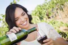 Junge erwachsene Frau, die ein Glas Wein im Weinberg gießt Stockfotografie