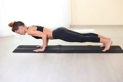 Junge erwachsene Frau, die eine Planke auf Yogamatte tut Lizenzfreies Stockbild