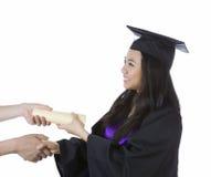 Junge erwachsene Frau, die ihr Diplom beim Graduieren empfängt stockbilder
