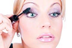 Junge erwachsene Frau, die Kosmetik aufträgt stockfotos