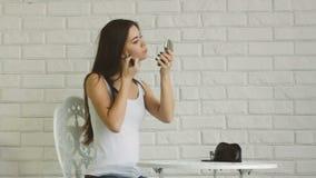 Junge erwachsene Frau, die Make-up durch tut stock footage
