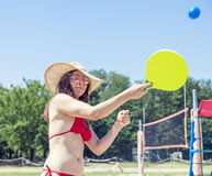 Junge erwachsene Frau, die Tennis auf dem Strand spielt Stockbild