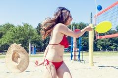 Junge erwachsene Frau, die Tennis auf dem Strand spielt Stockbilder