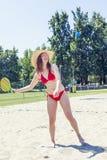 Junge erwachsene Frau, die Tennis auf dem Strand spielt Lizenzfreies Stockbild
