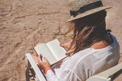 Junge erwachsene Frau mit einem Hut auf dem Strand ein Buch lesend Stockfotografie