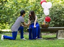 Junge erwachsene Frau riecht rote Rose von ihrem Liebhaber lizenzfreies stockfoto