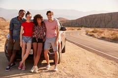 Junge erwachsene Freunde auf einer Autoreise eine Pause durch ihr Auto machen lizenzfreie stockfotos