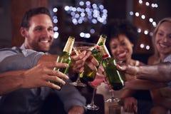 Junge erwachsene Freunde bilden einen Toast an einer Hausparty, Abschluss Lizenzfreies Stockfoto