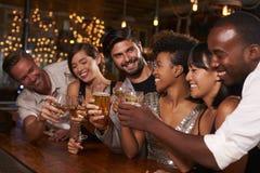 Junge erwachsene Freunde, die einen Toast durch die Stange an einer Partei machen lizenzfreie stockfotos