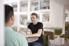 Junge erwachsene männliche Studenten, die im modernen Hochschulcafé sprechen stockfoto