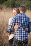 Junge erwachsene Paare, die draußen im hohen Gras umarmen Stockfotos