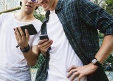 Junge erwachsener Mannesfreunde auf dem Basketballplatz unter Verwendung des smartphon lizenzfreie stockfotografie