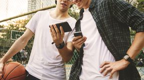 Junge erwachsener Mannesfreunde auf dem Basketballplatz unter Verwendung des smartphon lizenzfreies stockbild