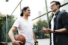 Junge erwachsener Mannesfreunde, die Basketball im Park spielen lizenzfreies stockfoto