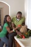 Junge ethnische Paare auf der Küche, die Lebensmittelgeschäfte sortiert Stockbilder