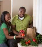 Junge ethnische Paare auf der Küche, die Lebensmittelgeschäfte sortiert Lizenzfreies Stockfoto