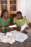 Junge ethnische Paare durch die Tabelle überwältigt durch Rechnungen Lizenzfreie Stockbilder