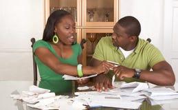 Junge ethnische Paare durch die Tabelle überwältigt durch Rechnungen Stockbild