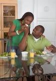 Junge ethnische Paare durch die Tabelle, die Frühstück isst Lizenzfreies Stockfoto