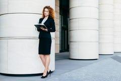 Junge europäische Frau mit dem gelockten Haar, tragendem schwarzem formalem Kostüm und Stöckelschuhen, ihr Tagebuch halten und sc stockfotografie