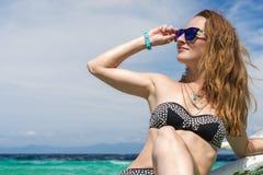 Junge europäische Frau mit Sonnenbrille sitzt auf dem Boot im tropischen Türkismeer und erhält Sonnenbräune am sonnigen Tag Lizenzfreies Stockbild