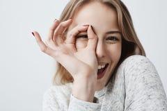 Junge europäische frohe blonde weibliche schauende Kamera durch Finger in der Okay-Geste Frau in der zufälligen Kleidung, lächeln Stockfoto