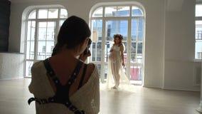 Junge europäische schwangere Frau im weißen peignoir auf Fotosession im Studio stock video