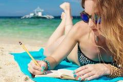 Junge europäische Frau mit Sonnenbrille liegt auf der Küste von tropischem Türkismeer und wrigting durch Bleistift im Notizblock Lizenzfreies Stockfoto