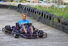 Junge fährt ein kart auf Stromkreis lizenzfreie stockfotos