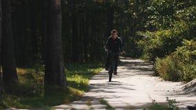 Junge fährt Fahrrad in Richtung zur Kamera entlang einer Straße in einem Wald und lässt Schuss stock video footage