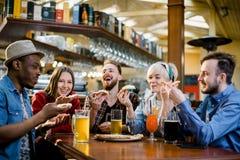 Junge fünf Pizza essende und beim Sitzen lachende Leute in einem Schnellrestaurant Gruppe Freunde, die wann genießen stockfotos